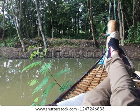 Lying on wooden cradle upon the natural pond among green forest #1247246833