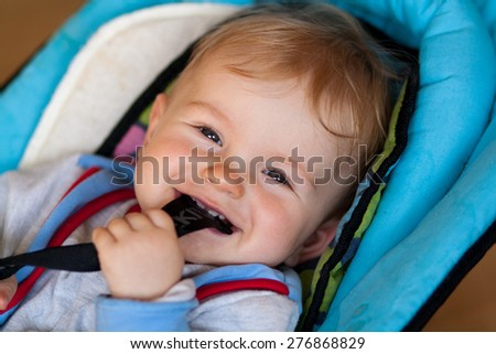lying small baby, smiling baby, baby has something in mouth, hold with teeth, lying in deck chair for baby