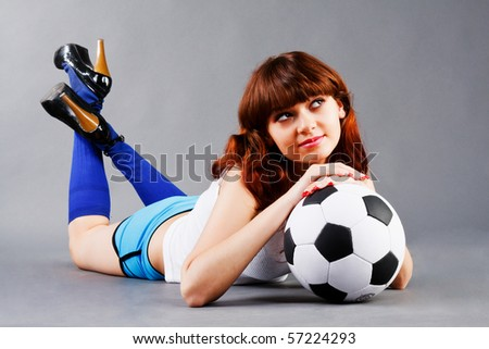 Lying young girl on floor with a soccer ball
