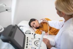 Lymph node ultrasiund probe. Ultrasound specialist in white robe making lymph node ultrasound test