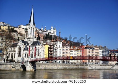 Lyon city with church and red footbridge in blue sky