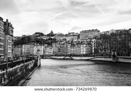 Lyon, France. Aerial view of Lyon in autumn with River and Bridge, France. Historical buildings with cloudy blue sky. Black and white #734269870