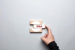 M&A merger and acquisitions concept. Male human hand pushing the wooden block with the word M&A and completing the merger process.
