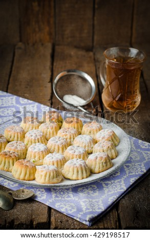 Maamoul or mamoul - arabic cookies stuffed dates with icing cugar on vintage wooden table background. Selective focus