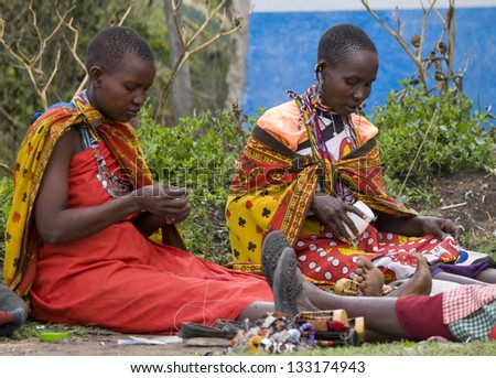 MAASAI MARA, KENYA-DECEMBER 27: Maasai women make traditional necklace 27 December, 2012 at Maasai Mara, Kenya. The Maasai are the most famous tribe in Africa.