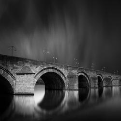 Maastricht, Saint Servatius stone bridge (Sint Servaasbrug) in black and white fine art style. Medieval arch bridge architecture in Maastricht, Limburg, the Netherlands.
