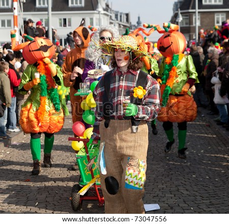 MAASTRICHT, THE NETHERLANDS - MARCH 6: Unidentified people in a Carnival parade dressed as pumpkins and scarecrow on March 6, 2011 in Maastricht, The Netherlands. This parade is organized yearly with 100,000 visitors