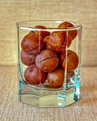 Macadamia nuts in a brown shell lie in a hexagonal glass made of transparent glass. The front part of the glass is in focus, the back part is blurred.