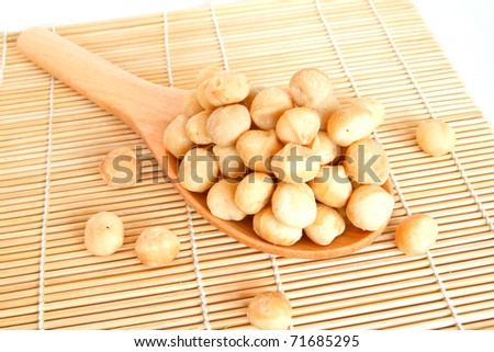macadamia nuts on wooden scoop isolated on white