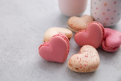 Macaron or French macaroon in heart shapes is a sweet meringue-based confection on gray background with copy space.
