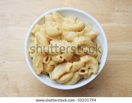 Macaroni and Cheese in a white bowl on a butcher block table