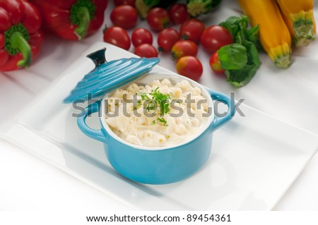 macaroni and cheese,kids favorite dish , on a blue little childish clay pot with vegetables on background