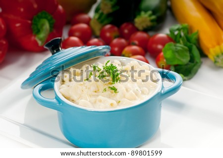 macaroni and cheese,kids favourite dish , on a blue little childish clay pot with vegetables on background