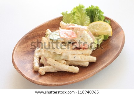Macaroni and vegetable salad on wooden plate