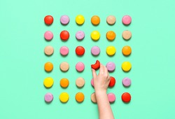 Macarons cookies aligned in a square shape, isolated on a green background. Woman hand grabbing an almond cookie. Eating french colorful macaroon.