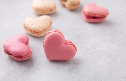 Macarons or French macaroons in heart shapes is a sweet meringue-based confection on gray background with copy space.