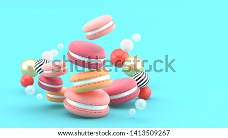 Macarons surrounded by colorful balls on a blue background.-3d rendering.