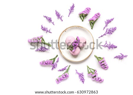 macaroons and flowers for light breakfast on white desk background top view