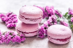 macaroons and mauve flowers for light breakfast on white desk background