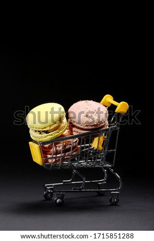 Macaroons in metal shopping basket. Studio Photo. Macaroons on dark background, colorful french cookies macaroons. Macaroons. Confectionery photography concept in black background portrait