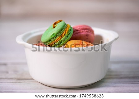 Macaroons of multiple flavors and colors: pink macaroons with strawberry, green macaroons with kiwi and beige macaroons with peaches filled with tasty whipped cream in a white porcelain bowl