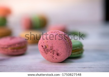 Macaroons of multiple flavors and colors: pink macaroons with strawberry, green macaroons with kiwi and beige macaroons with peaches filled with tasty whipped cream and decorated with almonds