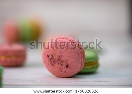 Macaroons of multiple flavors and colors: pink macaroons with strawberry, green macaroons with kiwi and beige macaroons with peaches filled with tasty whipped cream