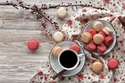 Macaroons on plate with cup of coffee, blossom brunch  on floral tablecloth and wooden white background
