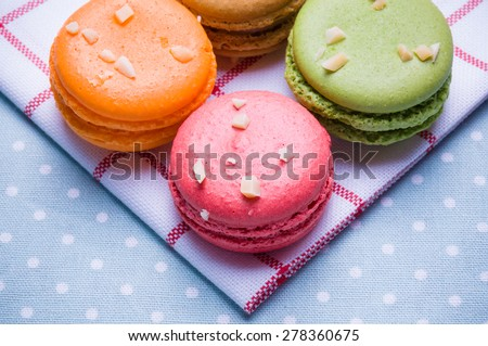 Macaroons put close together on blue table and white cloth with colorful and backlight.