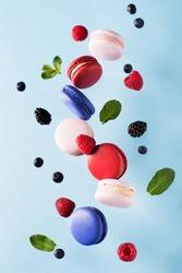 Macaroons, raspberries, blackberries and blueberries flying over blue background