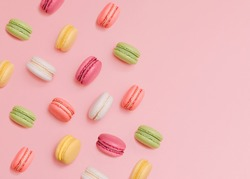 Macaroons Top view photo in minimal style Many colorful french biscuits on light pink background
