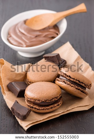 Macaroons with chocolate on wood table
