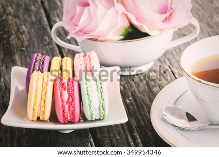 Macaroons with cup of tea and pastel rose in white cup on old wooden table - Vintage and vignette tone