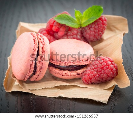 Macaroons with raspberries on a table