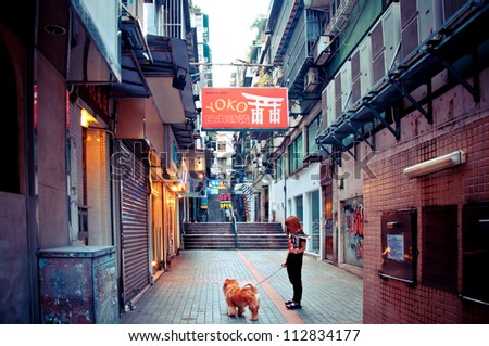 MACAU - AUGUST 1: person with dog walking in narrow street on August 1, 2012 in Macau, China. The Historic Centre of Macao was inscribed on the UNESCO World Heritage List in 2005