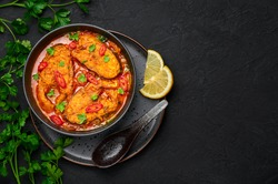 Macher Jhol in black bowl on dark slate table top. Indian cuisine Bengali Fish Curry. Asian food and meal. Top view. Copy space