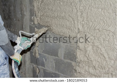 Machine application of plaster to the wall. Plasterer spraying plaster on wall. Professional, painting. Plastering walls in a new building
