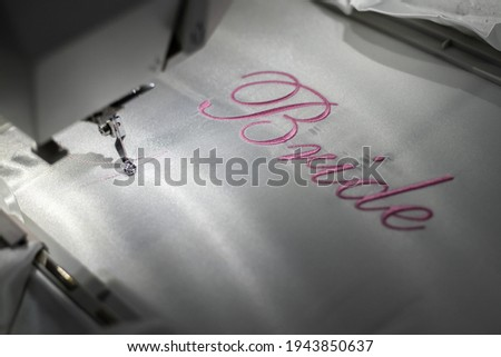 Machine embroider the inscription bride on a white satin robe. Inscription bride with pink thread. Wedding day preparation. Elegant bridal lingerie.White accessories for the bride.Glamorous style.