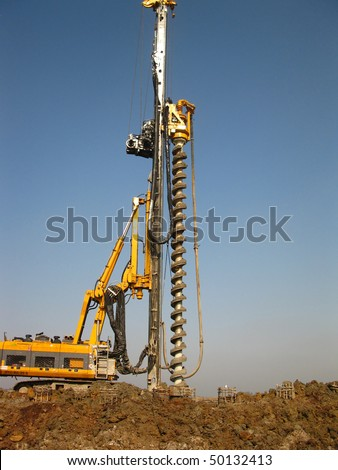 machine for drilling holes in the ground