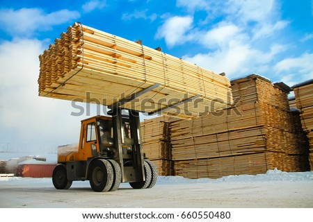 machine is lifting lumber on a wood factory