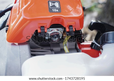 Photo of  Machine parts of a German-designed brand-new petrol brushsaw : detail of the soft button of the fuel pump on the carburator, linked to the gas tank with intake hoses, and the recoil starter behind