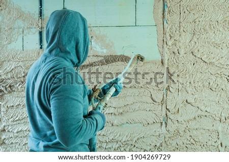 Machine plaster. Walls with gypsum plaster or cement plaster. Plasterer operating man sprayer equipment machine for spraying layer putty plaster finishing on brick wall.
