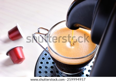 machine serving espresso coffee in a glass cup and two capsules on the table