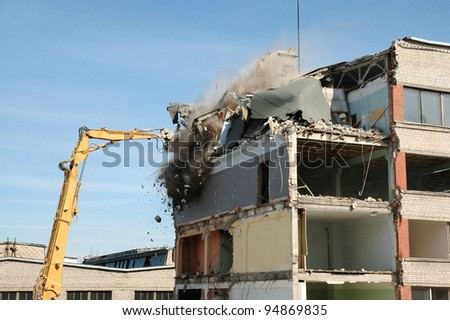 machine taking down an old building