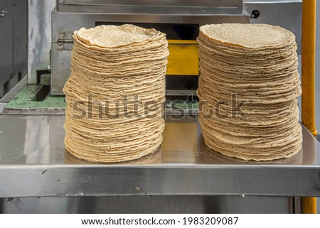 machine to make tortillas Mexican tortilleria with metal band and a kilo of tortillas wrapped in white paper Foto stock ©