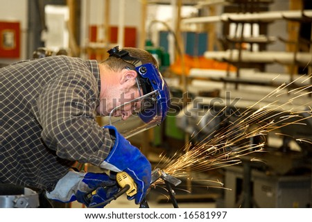 Machinist grinding metal in a factory.  Horizontal with room for text.  Authentic and accurate content depiction in compliance with industry code and safety standards.