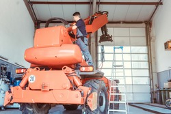 Machinist repairing a huge farm machine in his garage
