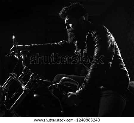 Macho, brutal biker in leather jacket riding motorcycle at night time, copy space. Man with beard, biker in leather jacket sitting on motor bike in darkness, black background. Night racer concept. #1240885240