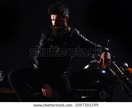 Macho, brutal biker in leather jacket stand near motorcycle at night time. Brutality and masculine concept. Man with beard, biker in leather jacket lean on motor bike in darkness, black background #1097301599