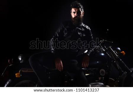 Macho, brutal biker in leather jacket stand near motorcycle at night time, copy space. Biker culture concept. Man with beard, biker in leather jacket lean on motor bike in darkness, black background. #1101413237